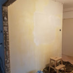 Me plastering some walls. This is the wall with the weird giraffey table.